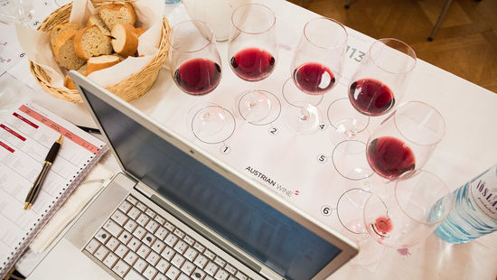 This picture shows a computer and some wine glasses filles with red wine