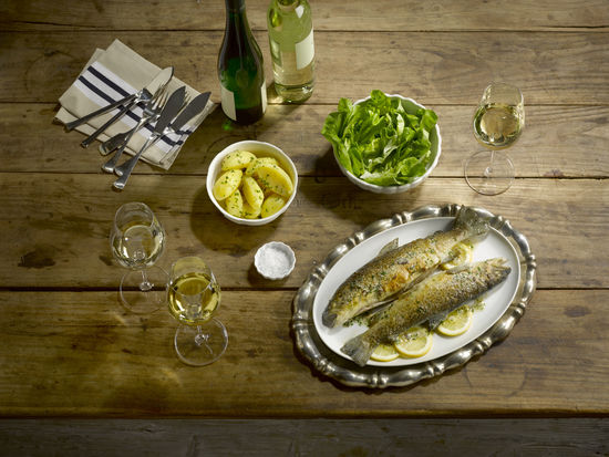 The picture shows trouts on a plate and three glasses of white wine