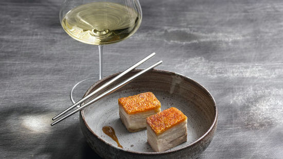 The picture shows slowly cooked pork belly and a glass of white wine.