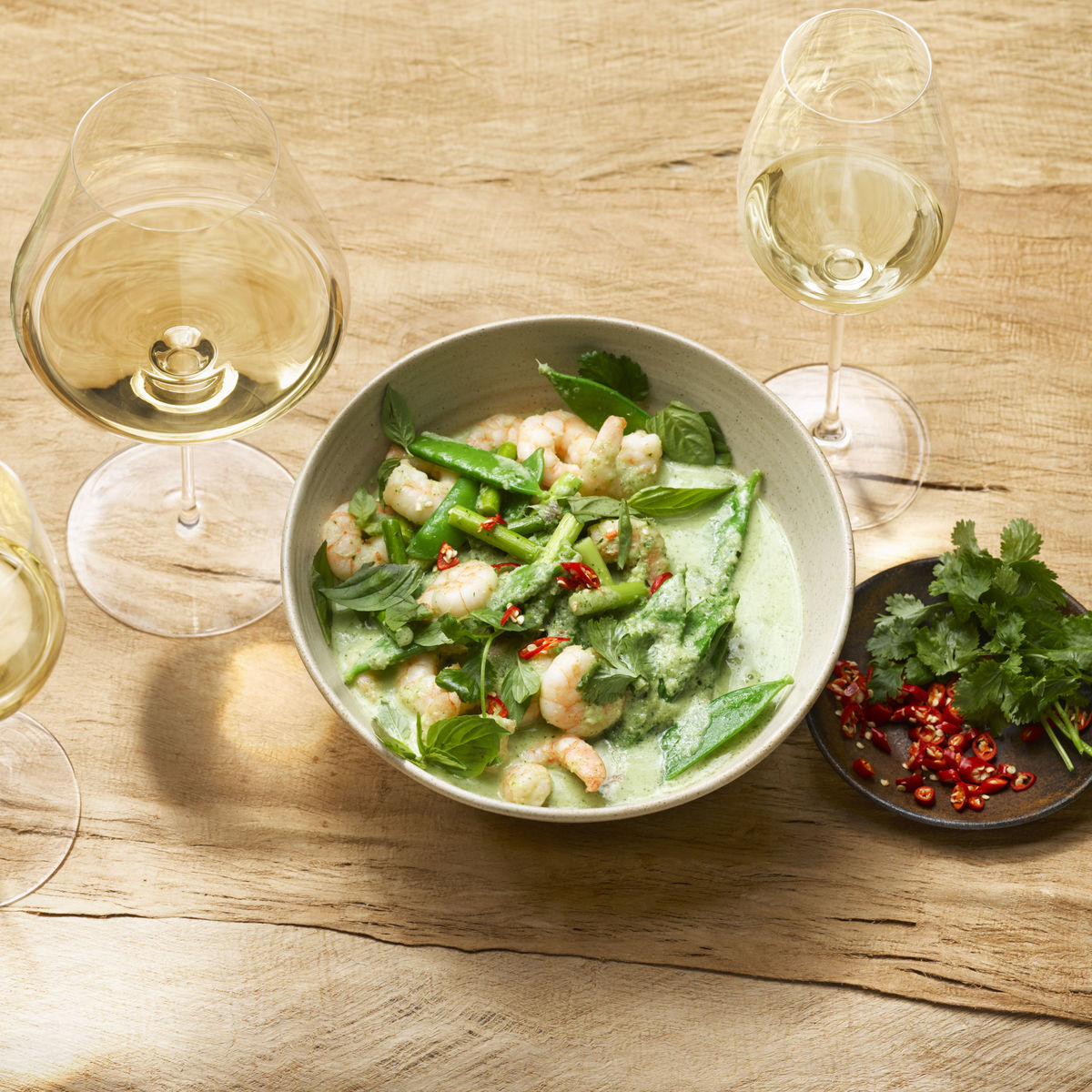 The picture shows green thai curry and three glasses of white wine.