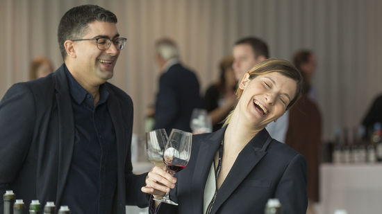 A picture shows two people tasting wine and laughing