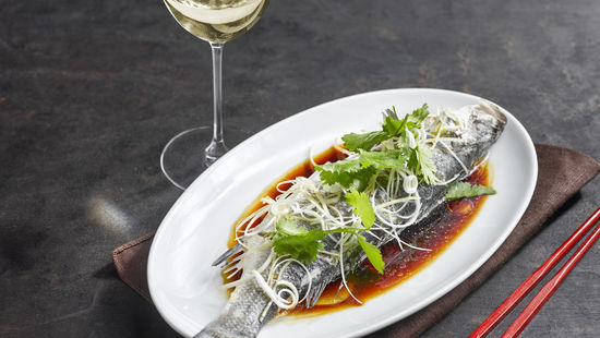 The picture shows Steamed Fish with spring onions and ginger and a glass of white wine.