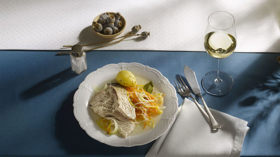 The picture shows carp and root vegetables on a plate and a glass of white wine