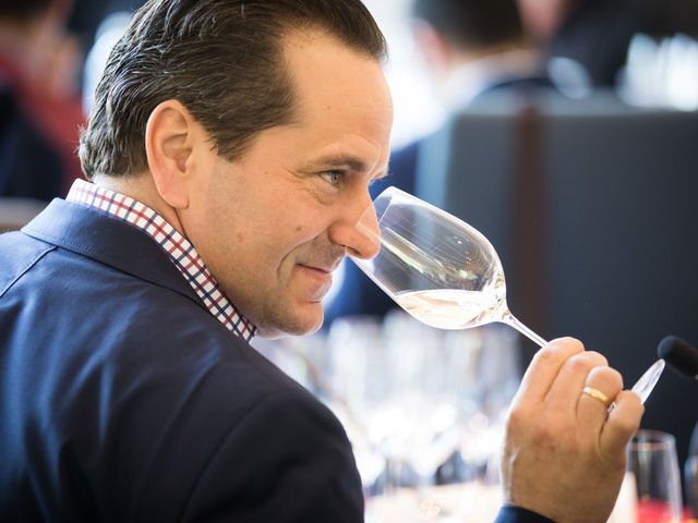 [Translate to English:] Sommelier Gerhard Retter riecht in das Weinglas