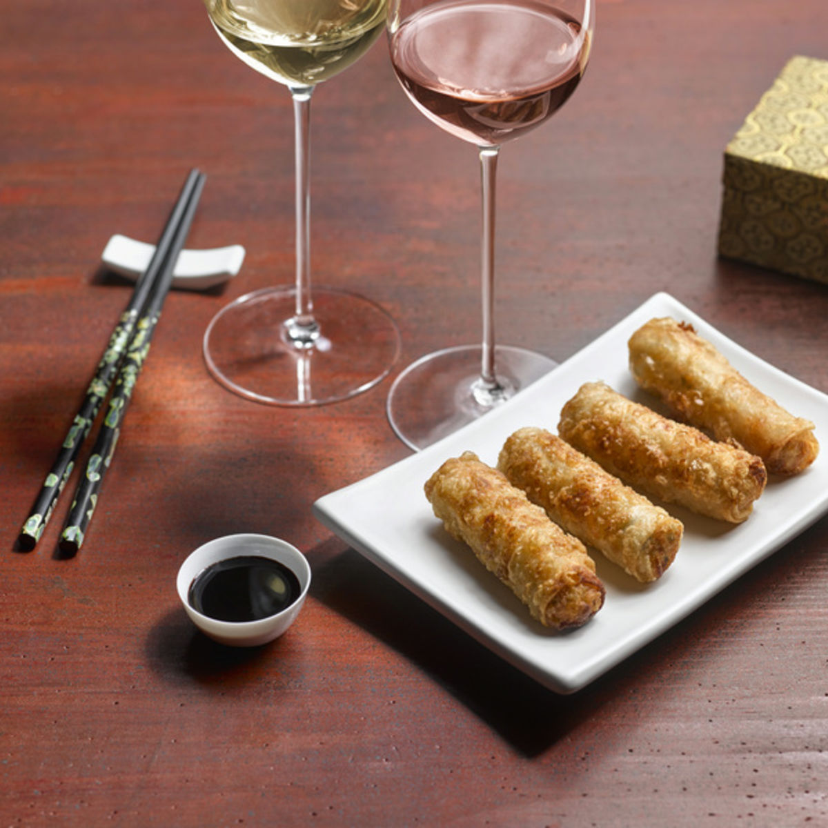 The picture shows fried spring rolls and two glasses, filled with white and rosé wine.