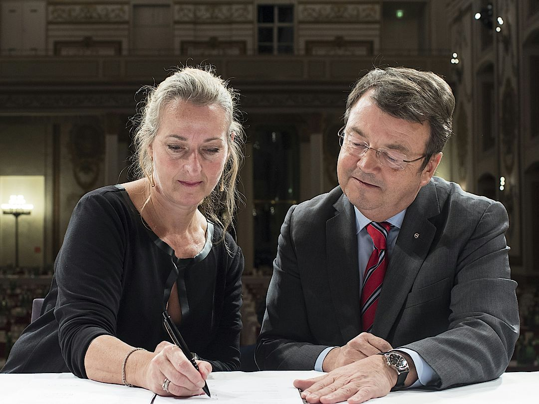 a picture shows the signing of a Partnership Agreement between Willi Klinger (Managing Director AWMB) and Penny Richards (Executive Director IMW)