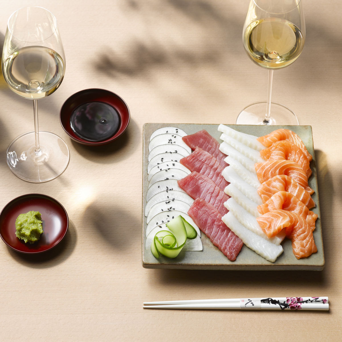 The picture shows sashimi and three glasses of white wine.