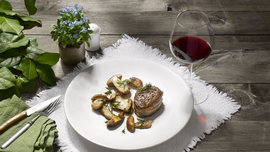 The picture shows sauteed porcini and a glass of red wine.