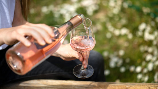 Rosé wine is being poured in a glas