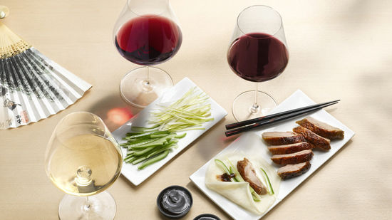 The picture shows the dish peking duck with three glasses of wine, filled with white wine and red wine.