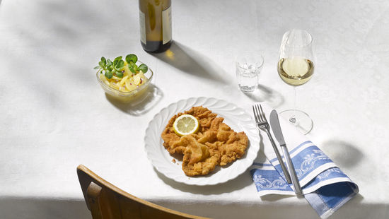 A picture shows a Wiener Schnitzel with potatoe salad and a glass of Austrian white wine.