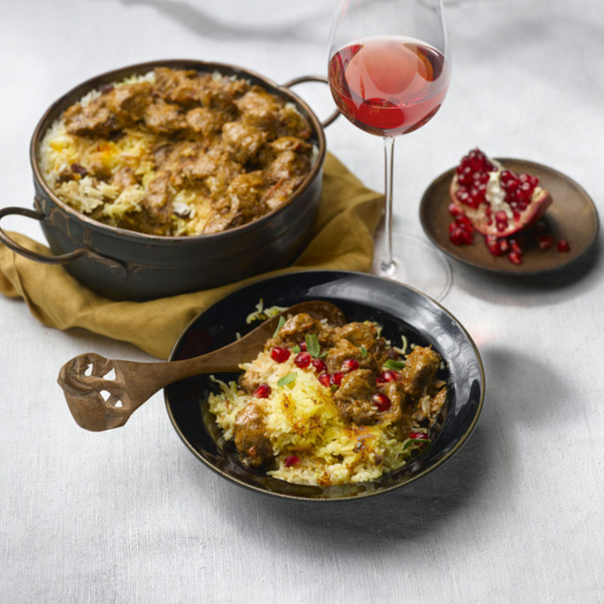 The picture shows the dish lamb biryani and a glass of rosé wine.