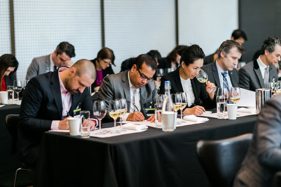 The picture shows a seated tasting with sommeliers.
