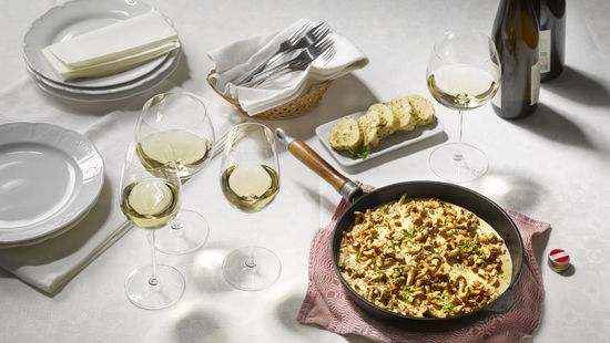 The picture shows a dish with chanterelle mushrooms and four glasses of white wine.