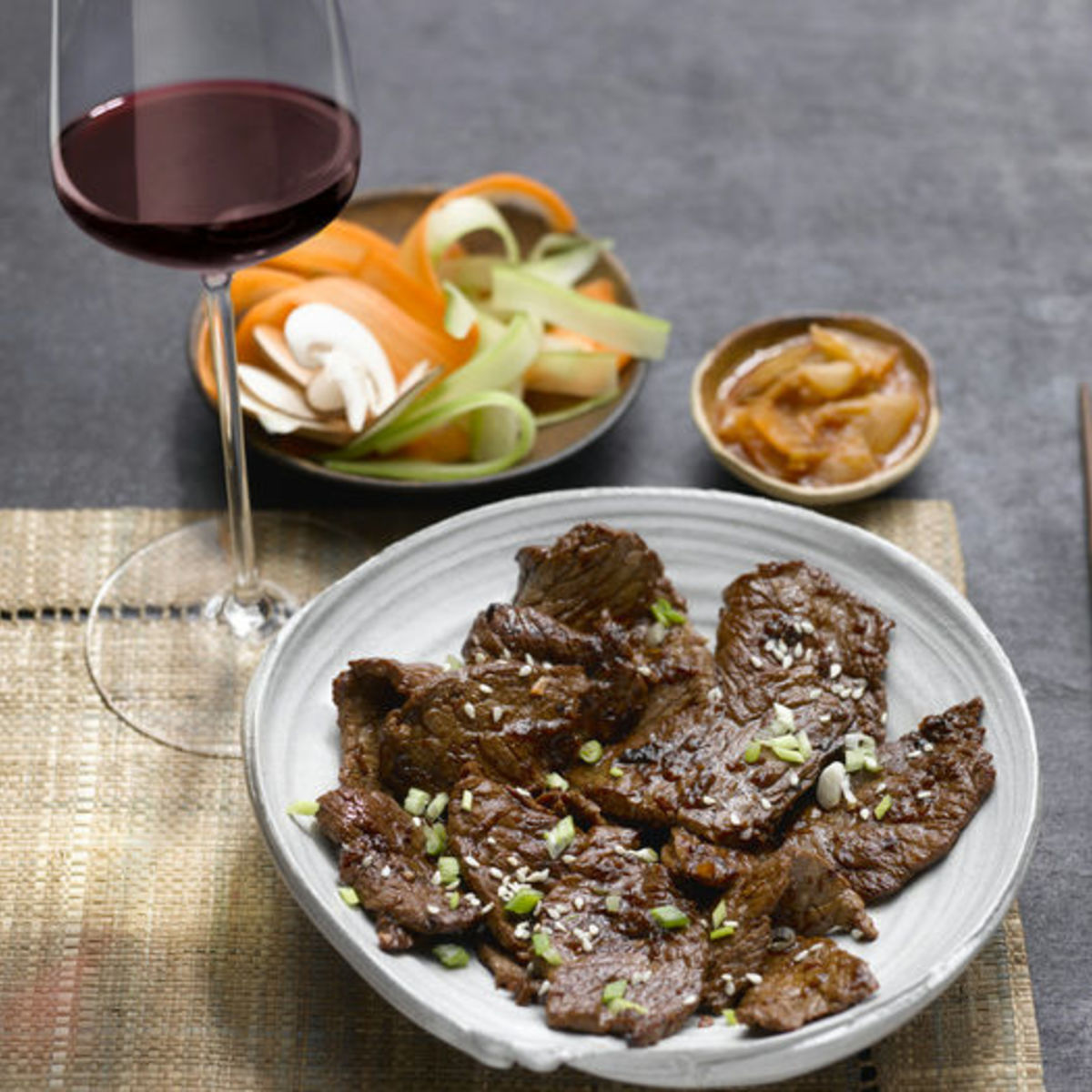 The picture shows the dish Bulgogi and a glass of red wine.