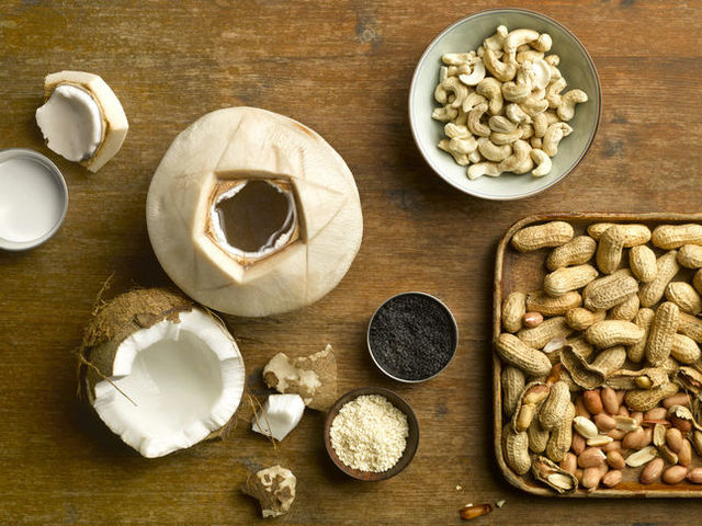 Coconut, cashews and peanuts on a table.
