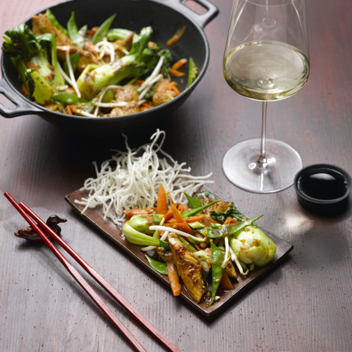 The picture shows a wok dish with a glass of white wine.
