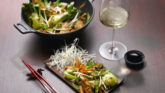 The picture shows a wok-dish and a glass of white wine.