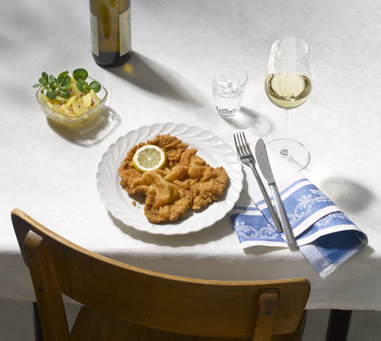 A picture shows a Wiener Schnitzel and a glass of white wine