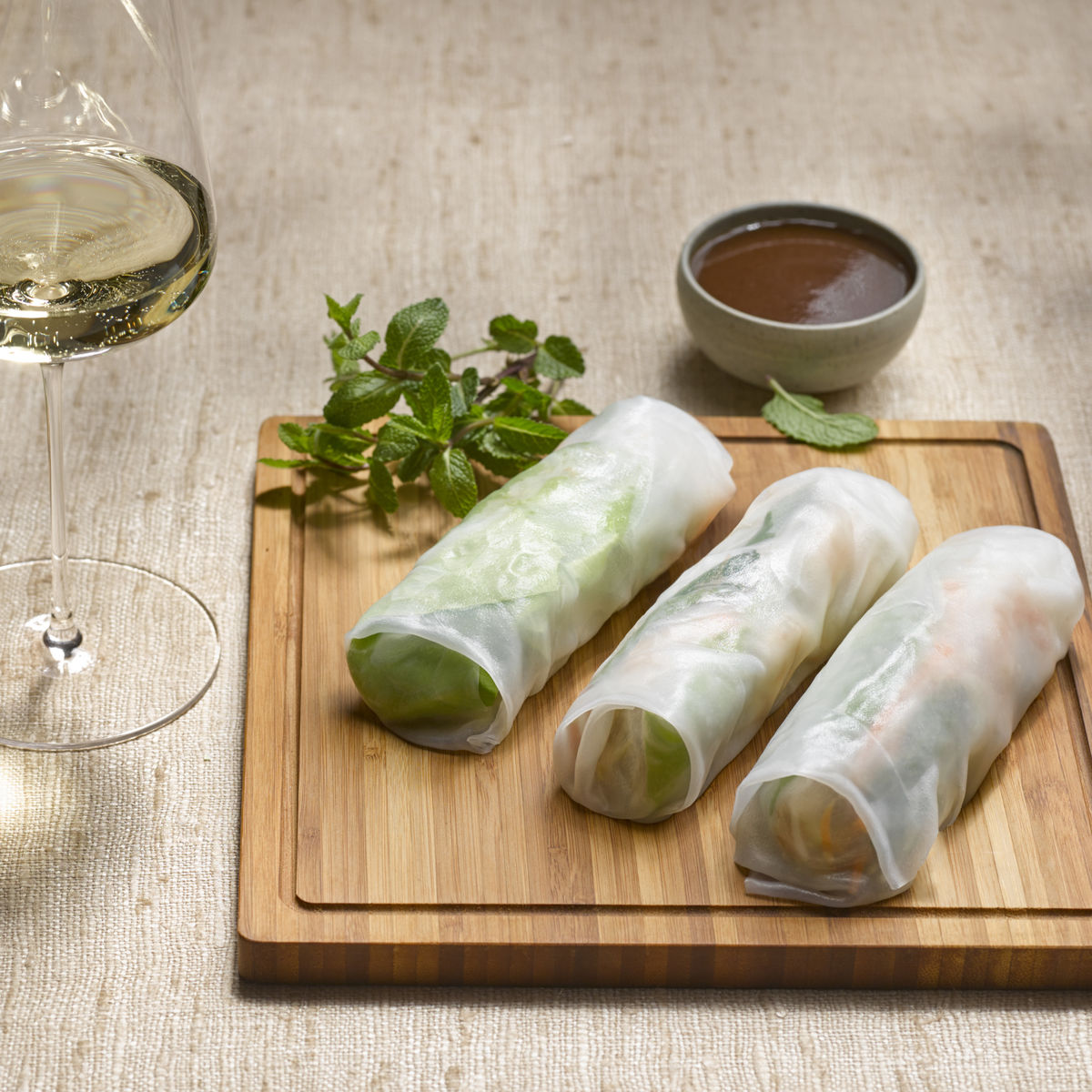 The picture shows raw spring onion and a glass of white wine,